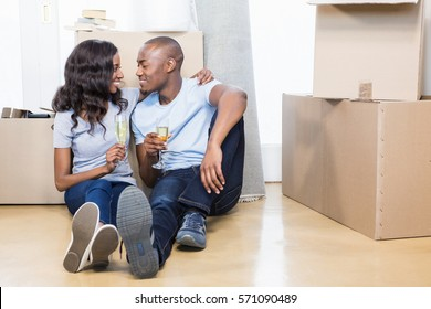 Portrait of young couple holding glasses of champagne in their new house