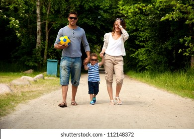 Portrait of a young couple holding their little son on their way to a summer destination