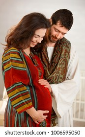 Portrait of young couple at home expecting baby, husband touching wife's pregnant belly.