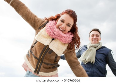 Portrait of young couple joyful with excitement on winter beach holiday, smiling energy travel lifestyle, carefree active. Boyfriend and girlfriend recreation, fun together travel, outdoors.