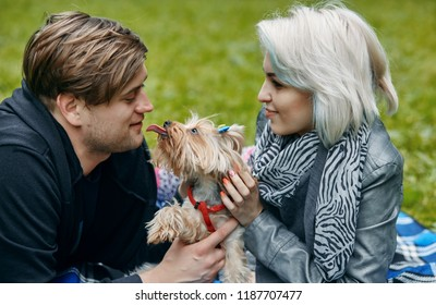 a Portrait of a young couple with a little dog