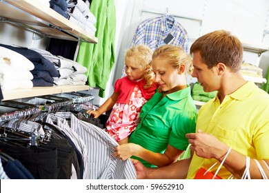 Portrait of young couple looking at clothes with their daughter in the mall