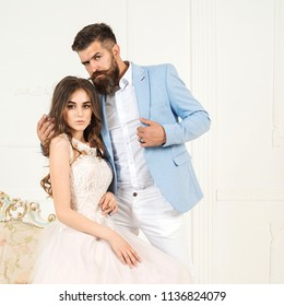 Portrait of young couple in love, dressed in classic clothes. Sexy elegant couple in tender passion. Beautiful woman near bearded man Sexy dominatrix woman posing and young macho lover in light tuxedo