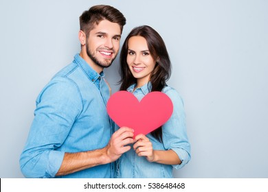 Portrait of young couple in love holding red paper heart.