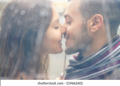 Portrait of young couple in love kissing under the rain with transparent umbrella - Handsome man and woman enjoying first date - Tender moments concept - Focus on girl face - Warm vintage filter