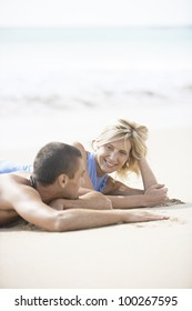 Portrait of a young couple in love laying down on a white sand beach.