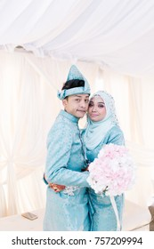 Portrait of young couple. Love story of handsome man and beautiful woman in Malay or Asian traditional dress.