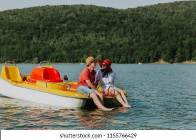 Portrait of young couple in love talking while pedal boating on the lake. Cheerful man and woman relaxing on pedal boat on hot sunny day.