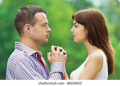 portrait young couple loving facing each other hold hands background summer green park