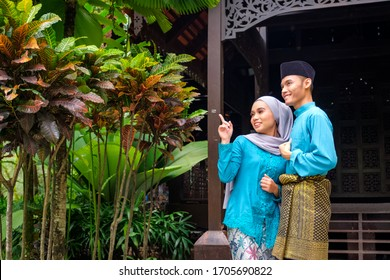 A portrait of young couple of malay muslim in traditional costume during Aidilfitri celebration by traditional wooden house. Raya and Muslim fashion attire concept.