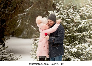 Portrait of young couple man and woman kissing in background of christmas tree with snow in winter Park
