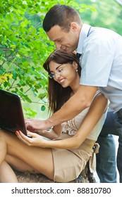 portrait young couple man woman student laptop background summer green park