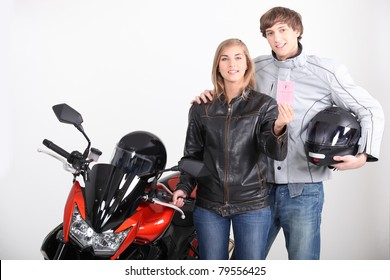 portrait of a young couple next to a motorbike