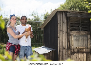 Portrait of a young couple on a farm with Chickens