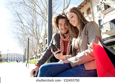 Portrait of a young couple on vacation in a destination city, sitting down with shopping bags to take a break and using a smart phone device during a sunny day.