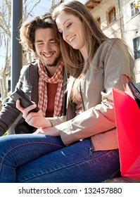 Portrait of a young couple on vacation in a destination city, sitting down with shopping bags to take a break and using a smartphone device during a sunny day.