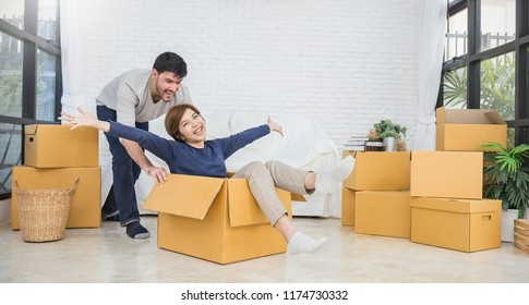 Portrait of young couple people man and woman have fun while moving to a new apartment. Boy pushes box with the girl. Happy interracial asian and caucasian people in the new house.