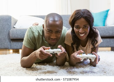 Portrait of young couple playing video game in their living room