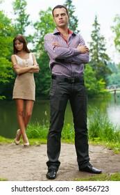 portrait young couple quarrel against summer forest lake
