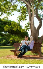 Portrait of young couple relaxing on wooden bench in park.