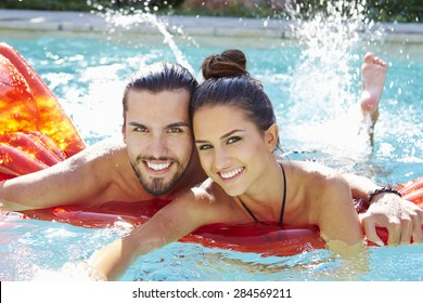 Portrait Of Young Couple Relaxing In Swimming Pool
