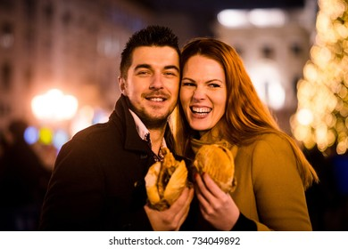 Portrait of young couple with sandwiches - outdoor in street with neon lights at night