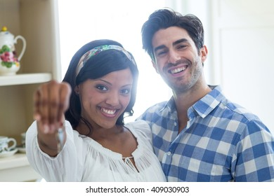 Portrait of young couple showing a key of their new house