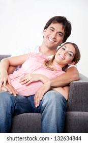 Portrait of young couple sitting close on couch.