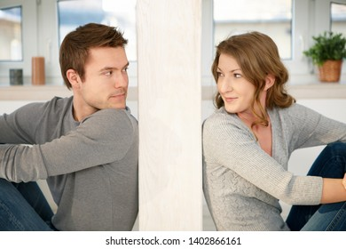 Portrait of young couple sitting and looking at each other at home.