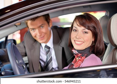 Portrait of young couple sitting in a new car at showroom
