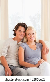 Portrait of a young couple sitting on a sofa in their living room