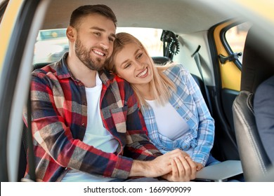 Portrait of young couple sitting in taxi