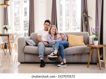Portrait of young couple smiling and enjoying together while sitting on the couch at home.