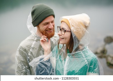 Portrait of young couple  standing and hugging under the rain in park on front of the lake in mountains. Beautiful couple spending time together. Travel concept