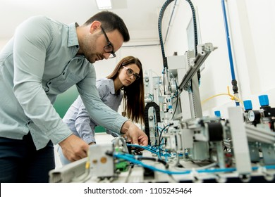 Portrait of young couple of students working at robotics lab