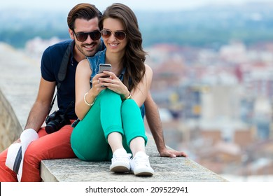 Portrait of young couple of tourist in town using mobile phone.