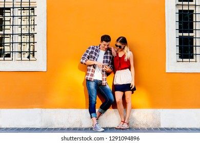 Portrait of young couple using mobile phone in the street. Mobile Concept.