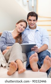 Portrait of a young couple using a tablet computer in their living room