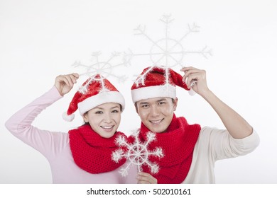 Portrait of young couple wearing Santa hats,holding snowflakes