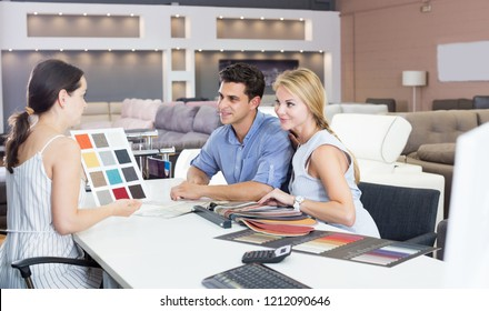 Portrait of a young couple who are consulting with the assistent about the choice of a color for new sofa