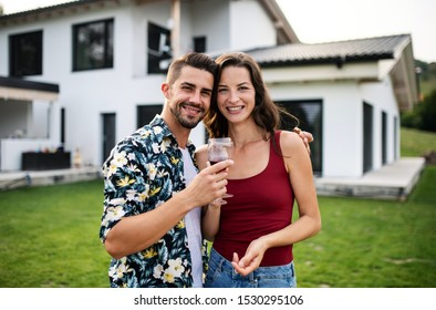 Portrait of young couple with wine outdoors in backyard, looking at camera.