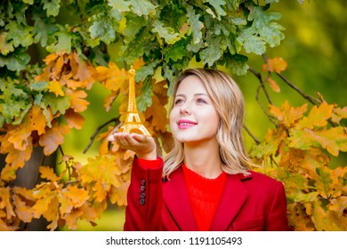 Portrait of a young cozy woman with Eiffel tower toy near oak tree in autumn season park.