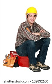 portrait of young craftsman sitting on toolcase