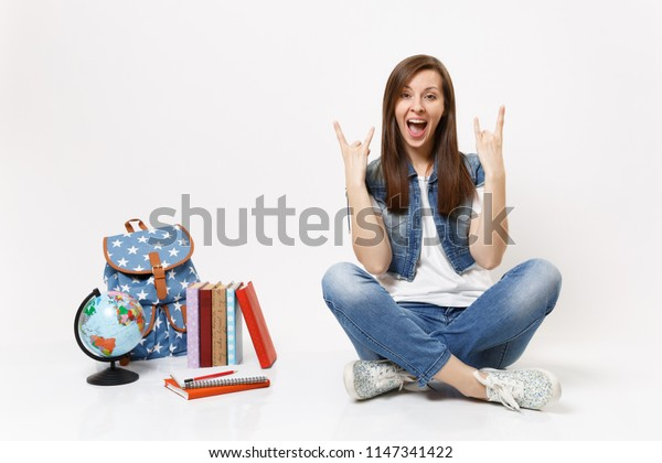 Portrait of young crazy overjoyed woman student showing rock-n-roll sign sitting near globe, backpack, school books isolated on white background. Education in high school university college concept