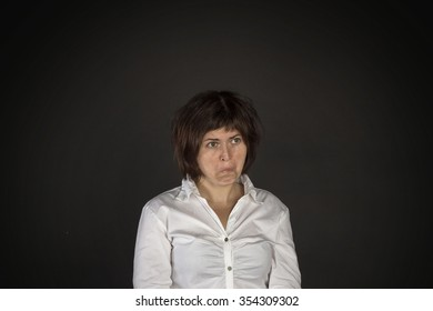 Portrait of young crazy surprised woman on black background