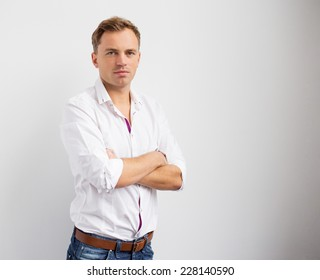 Portrait of young creative man standing with arms crossed