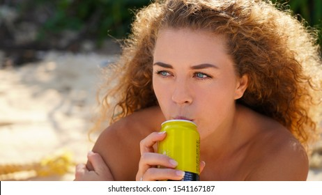 portrait of a young curly blue-eyed girl. beautiful girl drinks through a straw from a can. smile emotions
