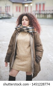 portrait of young curly woman posing in park during winter day – authenticity, youth, cheerful