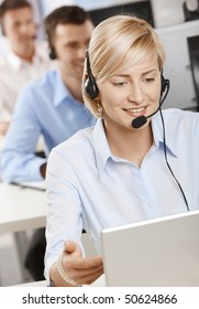 Portrait of young customer service operator talking on headset, smiling.