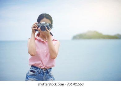 Portrait of young cute asian woman holding a vintage camera or film camera on her hand. travel or journey at summer sea. blurred blue sea at background. selective focus. filtered image
